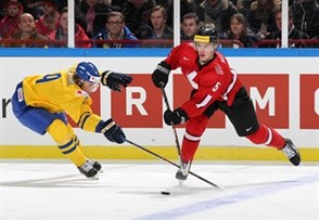 MALMO, SWEDEN - DECEMBER 26: Switzerland's Mirco Muller #5 makes a passe while Sweden's Jacob de la Rose #9 defends during preliminary round action at the 2014 IIHF World Junior Championship. (Photo by Andre Ringuette/HHOF-IIHF Images)